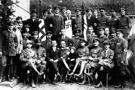 Julius Streicher is seated in the front row, to the left of the child, in this 1922 photo of Nazi Party members.