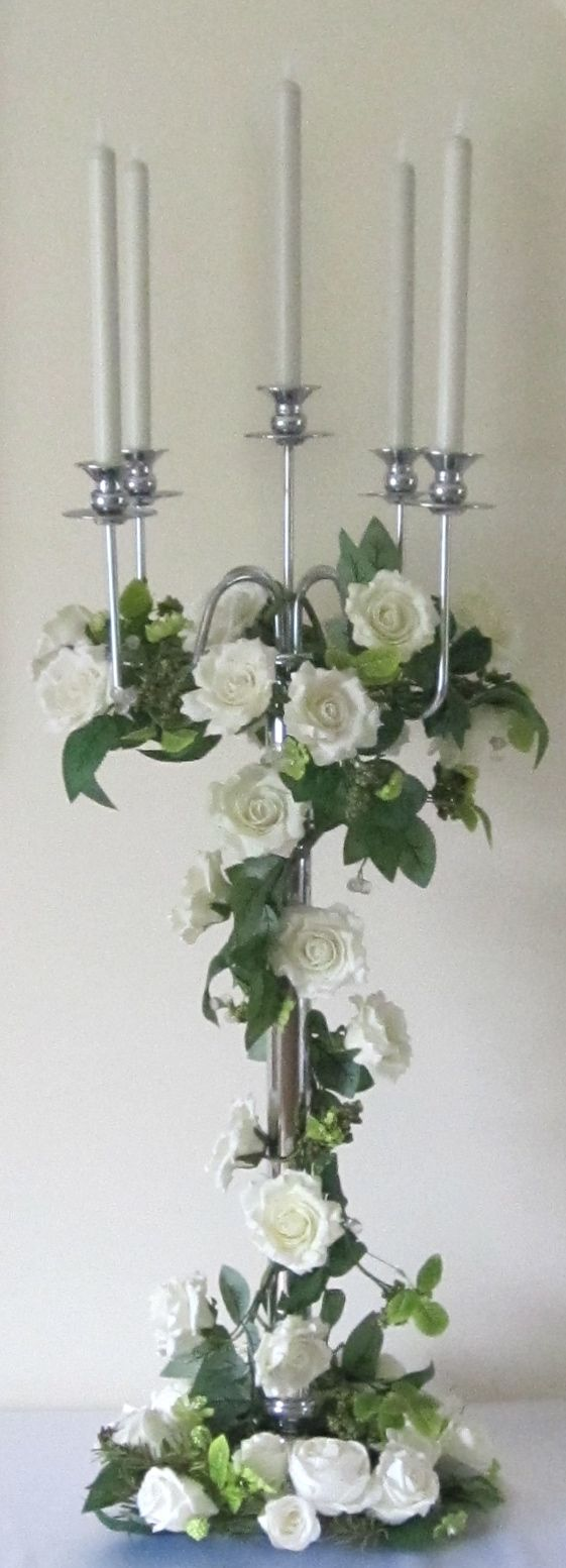 Ivory candelabra with wrapped greenery around centre and flowers in silk in colours scheme and draped amaranthus