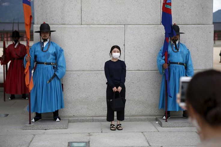 Chinese tourist wearing a mask to prevent contracting Middle East Respiratory Syndrome (#MERS) poses for photographs as men wearing traditional dress perform the daily reenactment of the changing of the Royal Guards, at the main entrance of the Gyeongbok Palace in central #Seoul, #SouthKorea, June 5, 2015.