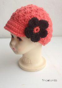 Una boina de crochet para bebé con flor Un gorro tipo boina de color mandarina.
