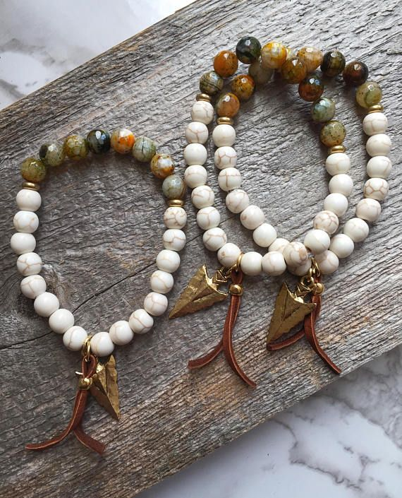 These Agate beads are gorgeous earthtone colors. Perfect for your Fall outfits. Combined with ivory magnesite beads and accented with gold spacers. A leather accent and gold arrowhead charm hang from the bracelet, giving this piece a free-spirit-boho feel. Approximately 7 inches in