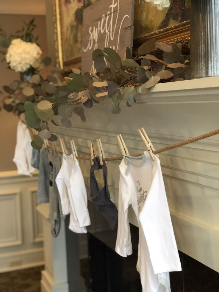 Baby Shower mantle decor Silver dollar Eucalyptus hydrangea and white roses. Clothes line with onesies and bibs. Greenery theme / gender neutral https://presentbaby.com