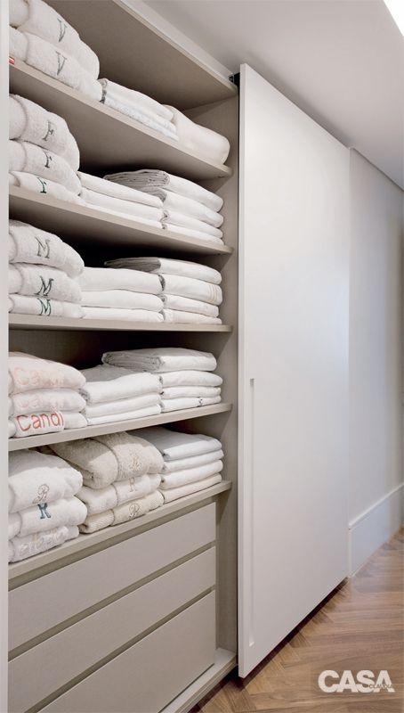 Organização: distribuição precisa de louças e enxoval - Casa - JOGOS CASADOS. Peças do mesmo kit de cama e banho são dobradas juntas, formando um pacote. Iniciais bordadas identificam os donos.
