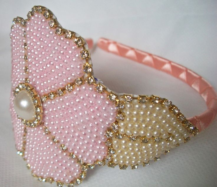 """Tiara da plástico encapada com fita de cetim rosa clara e decorada com uma linda flor de pérolas rosas e strass brilhoso.    Entre em contato através do link """"contatar vendedor"""" e encomende a sua para sua princesa!"""