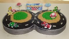 Mario Kart Birthday Party Cake using two round cakes covered in black frosting for the road, crushed graham cracker for the dirt, green frosting for the grass, and a checkered ribbon wrapped around the edges.  Mini Mario Kart racers in Yoshi, Mario, Luigi, and the Princess complete this cake perfectly.