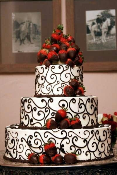 Chocolate dipped strawberries topped on a beautifully piped cake
