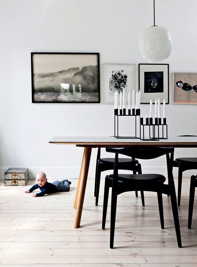 Spisebordet er fra Hay med sorte Wegner-stole med lædersæder til. De er fra Carl Hansen & Søn. Radiohus-pendlen over bordet har parret fundet brugt. Billederne er (set fra venstre mod højre) af Bent Holstein, Bo Valentin, en ukendt kunstner fundet på Lauritz.com og Cathrine Raben Davidsen.