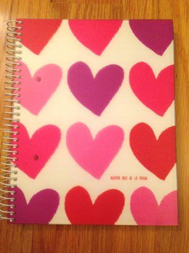 El cuaderno es rojo y rosado.