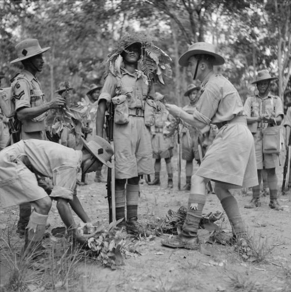 The British Army in Malaya, 1941. Men of the 2/9th Gurkha Rifles being instructed in the use of camouflage in the Malayan jungle, October 1941.