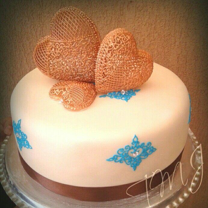 Barna-türkiz esküvői torta glazúr csipke díszítéssel./Brown and blue wedding cake decorated with lace frosting heart.