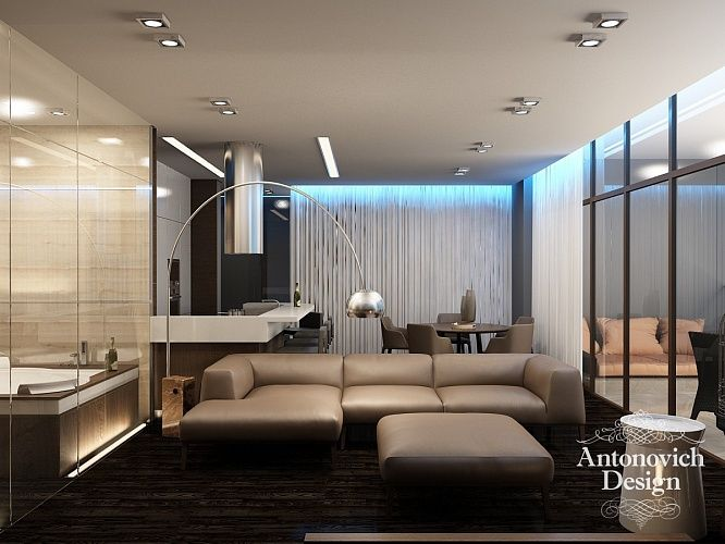 Мягкий диван в гостиной обит натуральной кожей, а снаружи отделан полосой тонкого шпонированного дерева. Прекрасный акцент в освещении апартаментов гостиной – авторские светильники стального цвета.