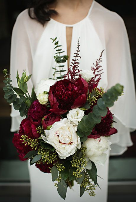 Brides.com: . A romantic bouquet comprised of white and burgundy peonies, accented with greenery, created by Ryder Sloan Events.
