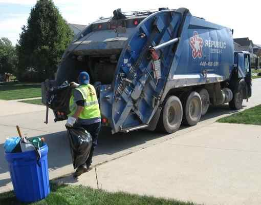 A Republic Services hurls garbage bags into the back of a truck collecting waste on Crossings Trail on Lorain's west side on Oct. 12, 2016. Lorain City Council has approved a city-wide switch to using automated garbage collection with wheeled cans, or carts, but the system likely won't be fully implemented in the city until spring 2017. Arwood Waste