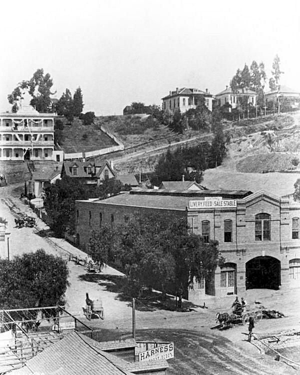 Take a look out of any window in Los Angeles today and it's hard to believe this place was ever a horse-and-buggy town. This shot was taken at the corner of 1st Street and Broadway in downtown L.A. circa 1890, where a stables and saddlery shop stands. Behind it, we can see the steep rise of Bunker Hill (which got lopped off half a century later.)