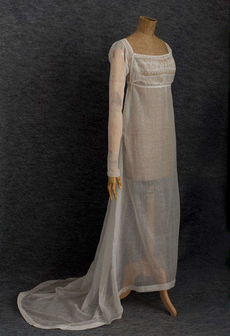 """Directoire-period cotton gauze dress, c.1800. The sheer cotton mull fabric (muslin) of the dress bears little resemblance to modern muslin. Originally made only in India, """"muslin"""" (c.1800) referred to a variety of cloths woven from very finely spun cotton yarns. The resulting cloth was transparent and gauze-like. The dress features a bib front bodice held in place with a pin on each side. The bodice and cuffs are embellished with handmade bobbin lace that has a drochel ground."""