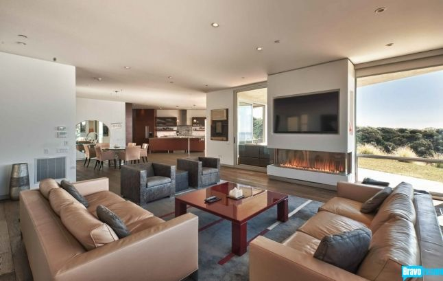 This modern living room seen on Million Dollar Listing Los Angeles with its clean lines and open floor plan warms up with a custom three sided fireplace.