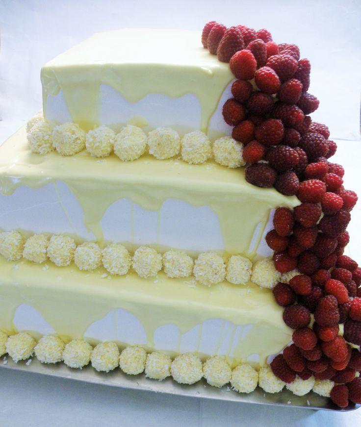 Tort 3-piętrowy oblany białą czekoladą z malinami
