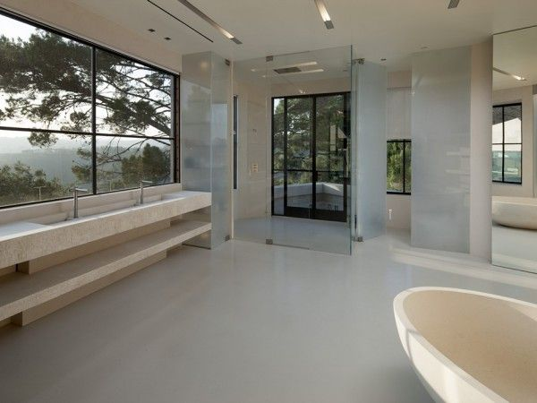 This incredibly spacious spa-style bathroom suite has a twin vanity unit, freestanding bathtub, and a walk-in waterfall shower.