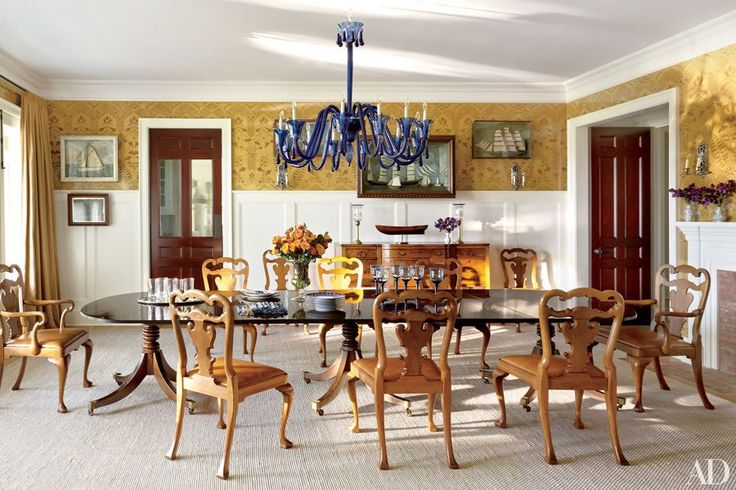 The dining room displays a collection of 19th-century ship dioramas; the custom-stenciled wall treatment is by Deirdre Newman, the 1940s Murano-glass chandelier is from Carlos de la Puente Antiques, and the rug is by Mitchell Denburg