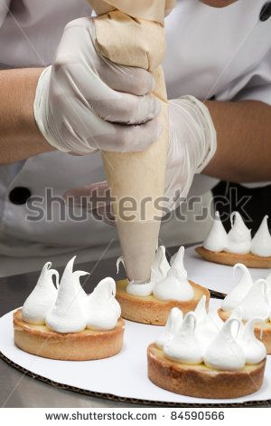 Cook topping the tartlets with meringue - stock photo