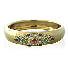 Cartier, circa 1994, bangle bracelet in 18K yellow gold featuring emeralds, rubies and sapphires accented by approximately 0.80ctw of diamonds. DESIGNER: Cartier MATERIAL: 18K Gold GEMSTONE: Diamond,