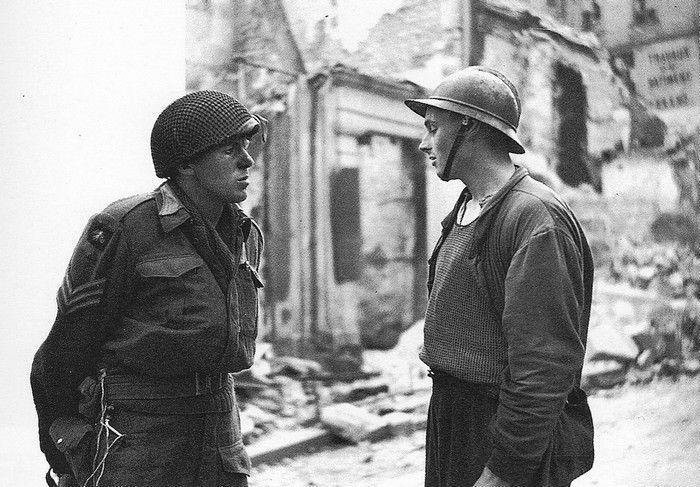 Caen: sergent Goddard, Army Film & Photographic Unit (AFPU), voir son badge d'épaule, dont la mère est française, s'entretient avec René Tithy, qui a été amputé d'un bras.
