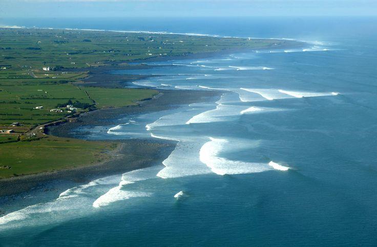 The Taranaki coastline, epic surf beaches, Cape Egmont Lighthouse looking on in the distance.