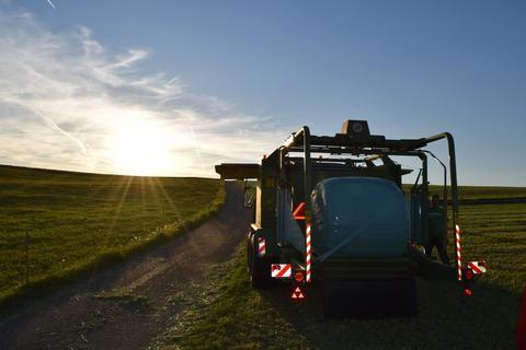 Pressen im Sonnenuntergang Zu sehen eine Krone Presse mit Claas Traktor im Sonnenuntergang beim 1. Schnitt.