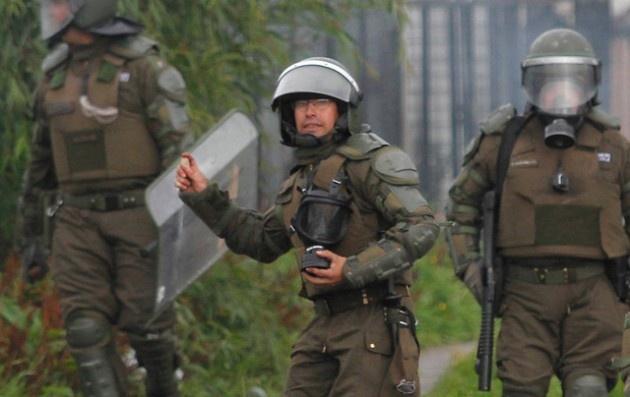 Carabineros diversificó su municiones en Aysén. En la imagen de Agencia Uno se ve a un efectivo policial haciendo uso de piedras para repeler a los manifestacntes en la jornada en que el gobierno determinó aplicar la Ley de Seguridad del Estado.