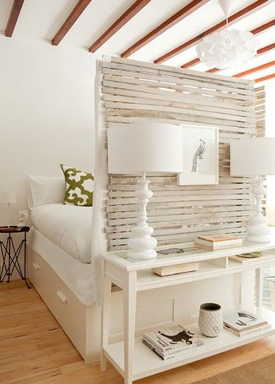 Make a higher footboard or place a mobile wall at the end of your bed creating dimension to the room and splitting up the space!