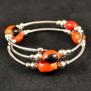 """Traditional Huayruro seed bracelet. Bracelet coils to expand and fit any size wrist.About the Huayruro:The huayruro is the seed of a tree native to Peru. To the Incas and Amazonian Indians, the rich red and black colors symbolize night and day, life and death. In Peru, the seed is used to attract good luck, and protect against negative energies. Relaxed diameter is 2"""". Stretched diameter is up to 5"""".Costume jewelry. Our jewelry is generally made of metal allo..."""