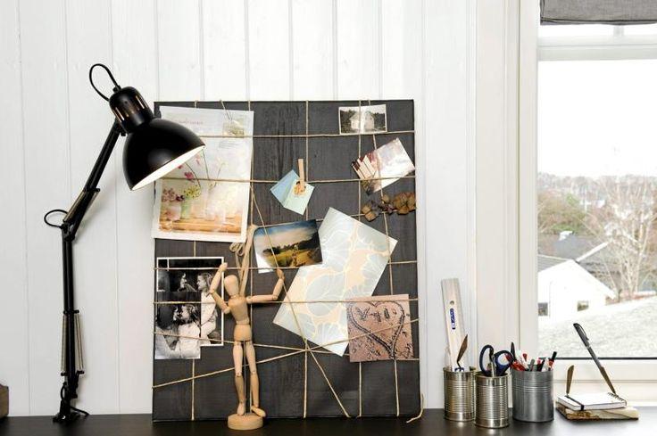 Oppslagstavlen er en finérpalte som er malt svart. Ved å feste hyssing rundt på kryss og tvers kan man henge opp ting med klesklyper eller binders. Eieren har brukt hermetikkbokser til oppbevaring av skriveutstyr, og kontorlampen fra Ikea er malt svart.