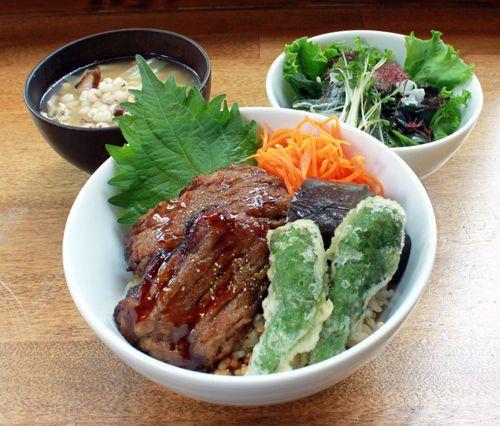 精進うなぎ丼(ベジうな丼)玄米ご飯に、ベジのうなぎを乗せ、さらに甘辛ナス煮、人参の塩麹炒め、ししとうの天ぷらが乗っかります。もちろん、サラダ、味噌汁付き!ごぼうに山芋、豆腐に、ゴマを擦って練り上げ、海苔を付けて整形し、油で揚げて、さらに焼いてタレを付けて、、、と、手間のかかるお料理