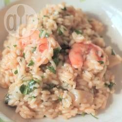 Het geheim van een goede risotto met zeevruchten is om een goeie kwaliteit visbouillon te gebruiken en superverse zeevruchten. Kook de zeevruchten en de rijst apart van elkaar, omdat de rijst meer tijd nodig heeft om gaar te worden en je anders de coquilles en garnalen veel te lang bereid en ze taai worden. Je kunt de garnalen ook vervangen door bijvoorbeeld inktvis of mosselen.