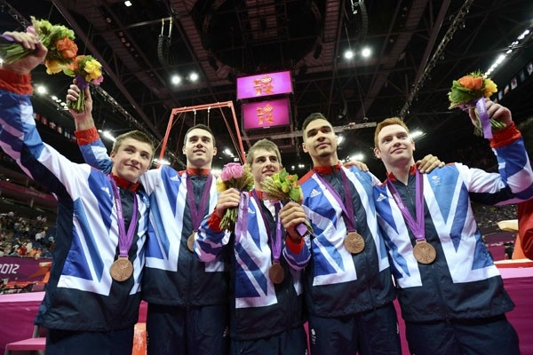 From left to right, Sam Oldham of Britain and teammates Kristian Thomas, Max Whitlock, Louis Smith, Daniel Purvis celebrate winning a bronze in the men's gymnastics team final in the North Greenwich Arena during the London 2012 Olympic Games on July 30, 2012.