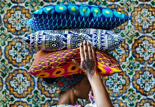 Een vrouw met henna tatoeages op haar handen draagt kleurrijke kussens met patronen die gebasseerd zijn op batik techniek op haar hoofd.