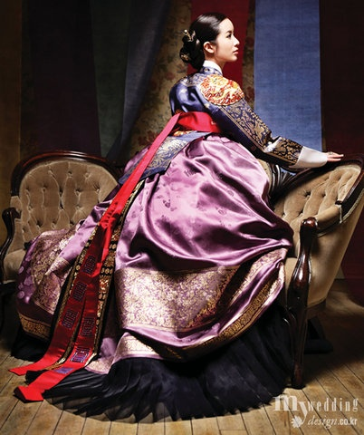 Korean dress (modern hanbok), the embroidery on the shoulder of this soreybok suggests that this could be the Queen. They would denote rank on the shoulders, chest and back of a garment.