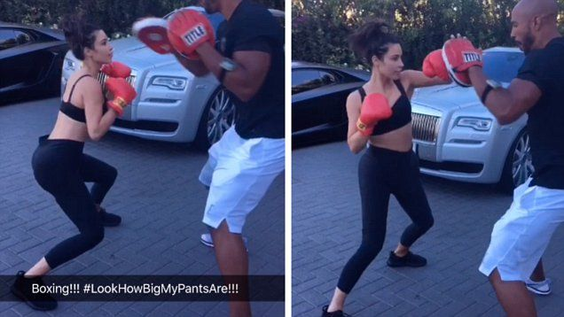 Kim Kardashian shows off her 70 lb thinner body by boxing with her trainer.