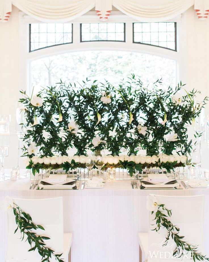 Talk about a conversation starter! We love how this vine-covered trellis #centrepiece was paired with the row of individual white #roses to create a modern, graphic #tablescape that still feels classically romantic.   Photography By: Simply Sweet Photography   WedLuxe Magazine   #wedding #luxury #luxurywedding #weddinginspiration #floral #centerpiece #decor #decordesign