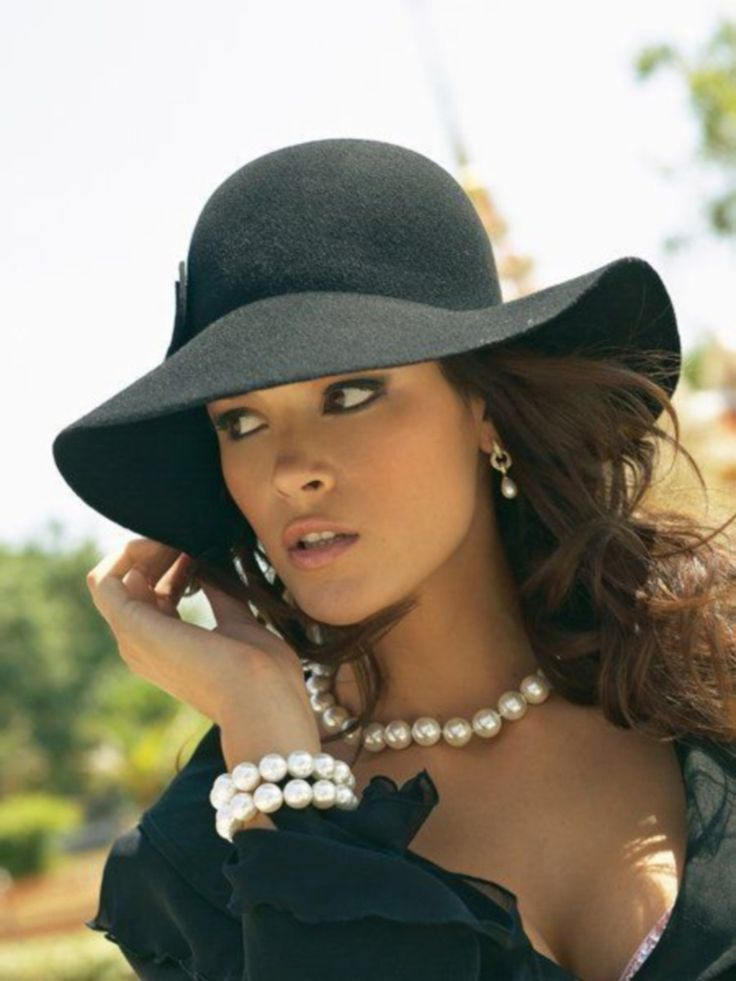 large pearl necklace & bracelets, small pearl earrings, tanned skin, ruffled LBD, charcoal floppy hat