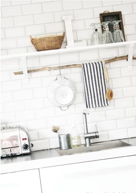 A branch propped between two shelf supports makes an instant kitchen storage rail with the addition of S hooks.