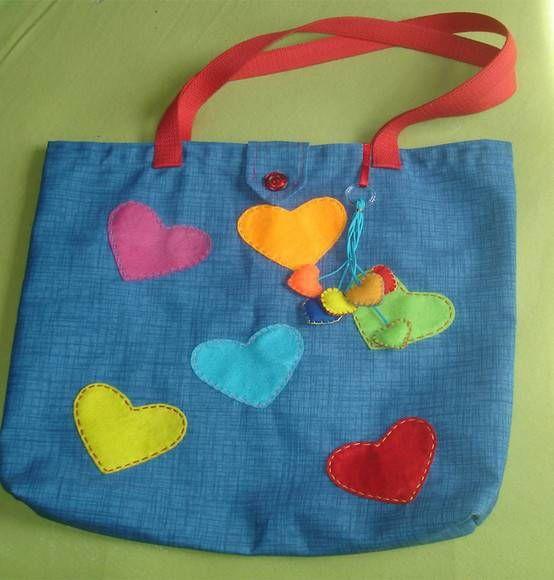 Bolsa em lona azul, forrada, com bolso interno para celular, botão, coraçõezinhos em feltro pendurados e com aplicações de corações em feltro. As bolsas medem, em média, 45 L x 39 A.  Super resistentes! R$ 42,00