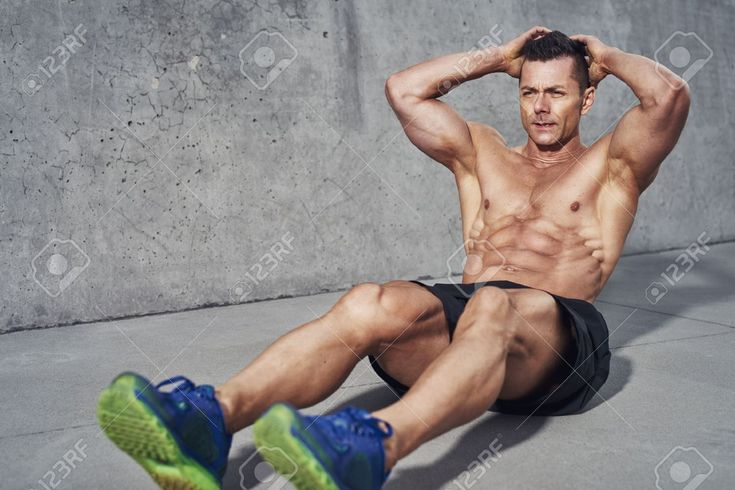 Male fitness model doing sit ups and crunches exercising abdominal muscles, six …