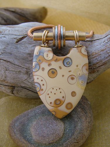 Polymer clay focal bead with brass tubing and copper, brass and silver washers to give movement to the piece.