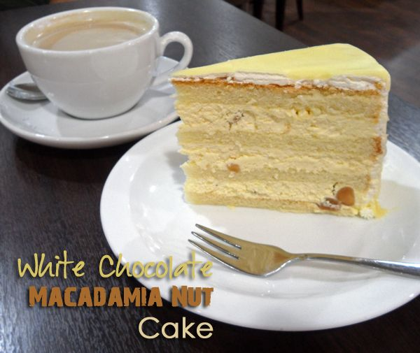 In this White Chocolate Macadamia Cake spongy cake layers are filled with fluffy coconut Swiss meringue buttercream and encapsulated in a rich white chocolate ganache glaze.
