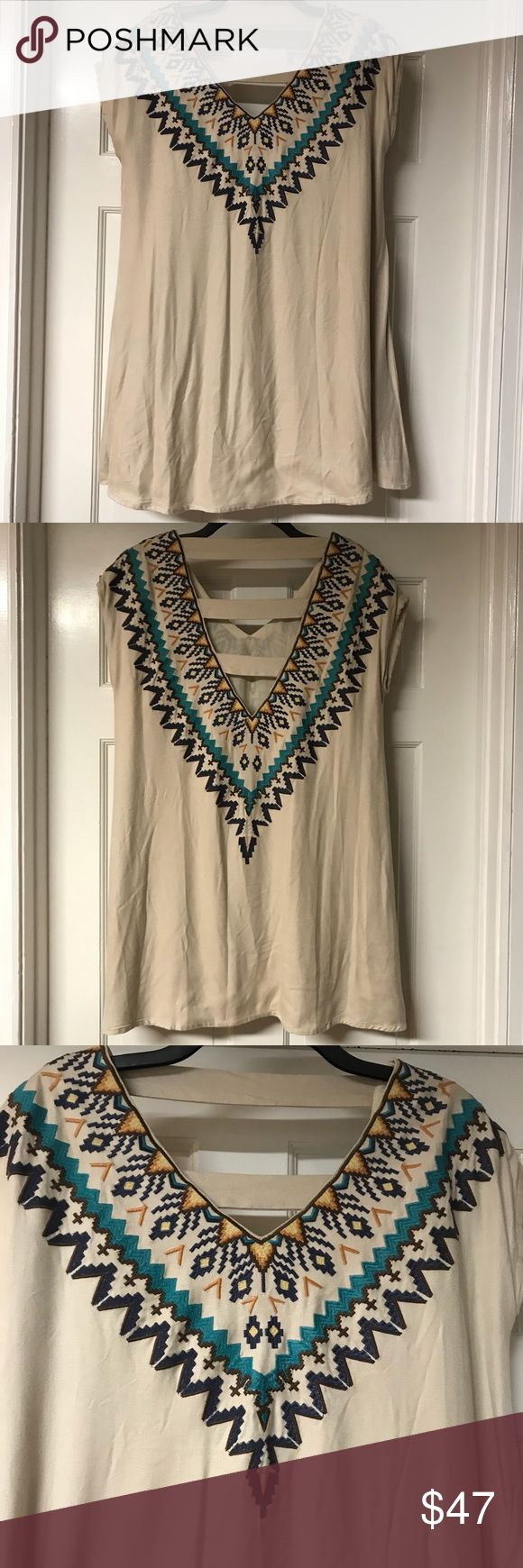 """JUDITH MARCH EMBROIDERED TUNIC Like new, linen colored, swing style, tunic with wrap around embroidered Aztex design in blue, turquoise, brown, yellow and orange on the front and  back. This stylish, V-neck top by Judith March has cap sleeves, a deep-V ladder back and is fully lined. Top 100% viscose, lining 100% polyester. Approximate measurements: chest 21"""", length 33"""". Judith March Tops"""