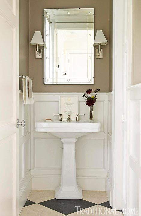 Putty-colored walls above white paneled wainscoting keep the mood serene; a checkered floor lends timeless style.