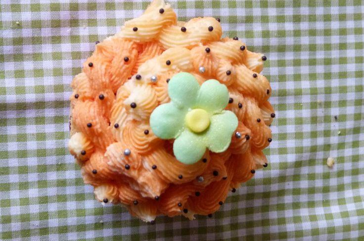 Cupcake decorado con buttercream de naranja y delicadas perlitas de chocolate y con una flor de fondant.