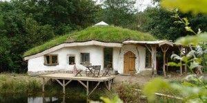 Prírodný domček postavený z balíkov slamy s dreveným interiérom a zelenou strechou