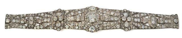 Bracelet. En or gris 18k et argent orné d''un ruban souple en chute, articulé et ajouré de motifs rayonnants ou géométriques sertis de diamants taillés à l'ancienne, à motif central interchangeable, l'un serti de diamants taillés en rose, le second plus important serti au centre de deux diamants ovales et d'un diamant demi-taille. Epoque 1930. Dans son écrin de la maison Auger à Paris chiffré L.V. Provenance: Famille du Maréchal Oudinot.